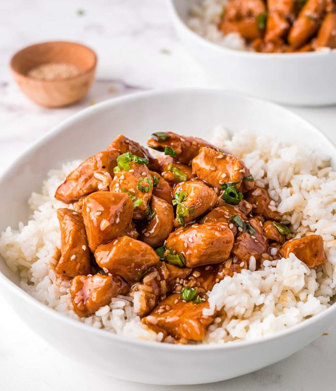 side view of bowl of rice topped with bourbon chicken