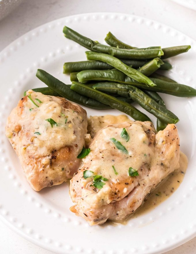 two chicken thighs on plate topped with creamy mustard sauce