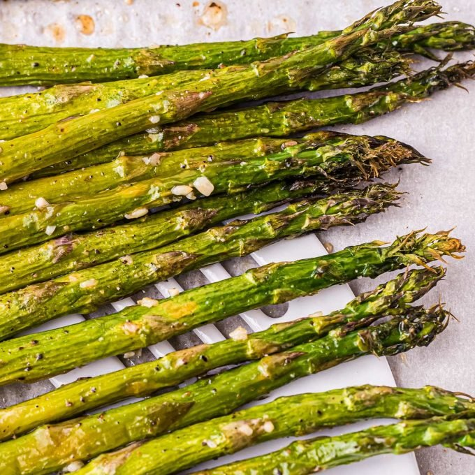 using a spatula to pick up roasted asparagus from a baking sheet
