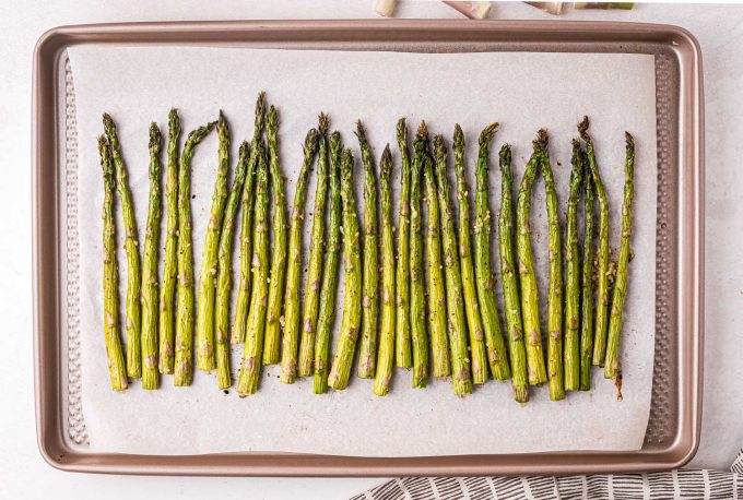 roasted asparagus spears lined up on baking sheet