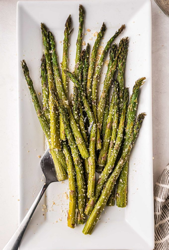 Here's a step-by-step guide for how to roast asparagus in the oven! This easy roasted asparagus recipe is ready in under 30 minutes, and uses simple, easy to find ingredients. It's just the best way to cook asparagus! #asparagus #roasted #vegetable #oven #baked