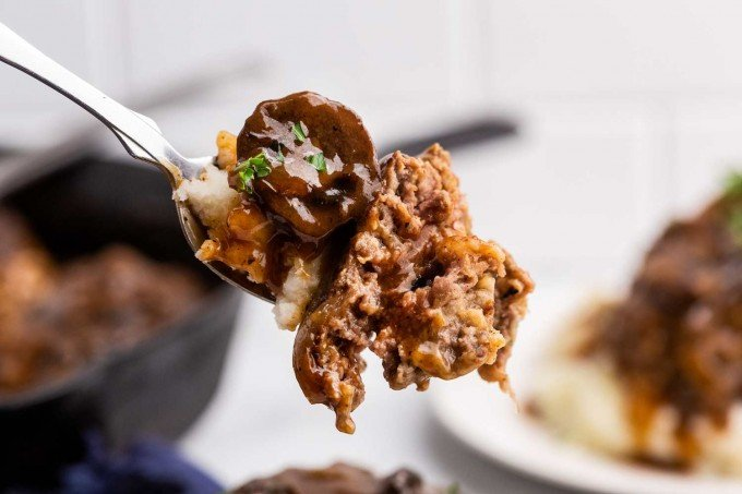 forkful of salisbury steak with mushrooms and mashed potatoes