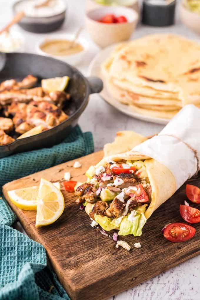 table spread with chicken shawarma wraps