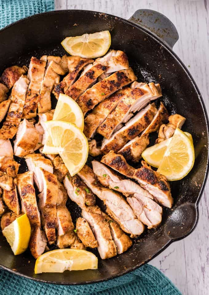 sliced chicken shawarma in cast iron skillet with lemon wedges
