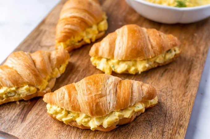 egg salad on croissants on cutting board