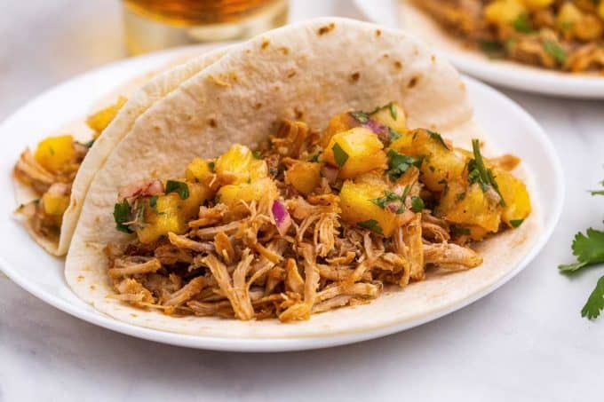 carnitas tacos with pineapple salsa on white plate