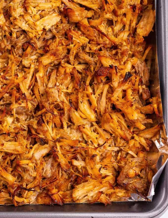 crispy edges of pork carnitas on baking sheet