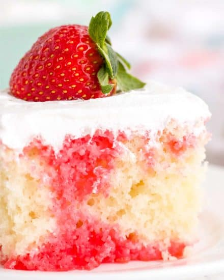 This Strawberry Poke Cake is the easiest and most delicious summer dessert around! Fluffy white cake is infused with strawberry jello, then slathered with whipped cream! Naturally a make ahead dessert, this is a dessert recipe the whole family will love! #pokecake #strawberrydessert #whitecake #dessert #baking #summerdessert