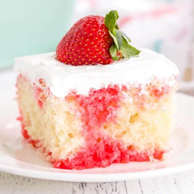 slice of strawberry poke cake on white plate