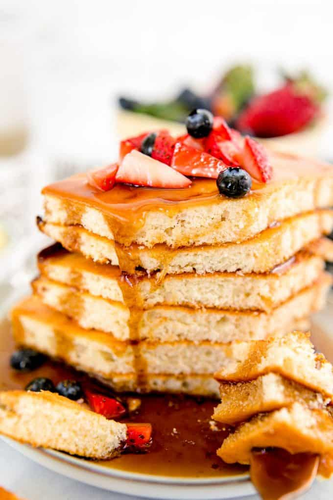 eating a stack of sheet pan pancakes with berries and syrup