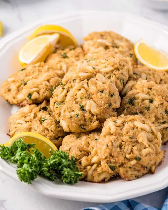 platter of crab cakes with lemon wedges