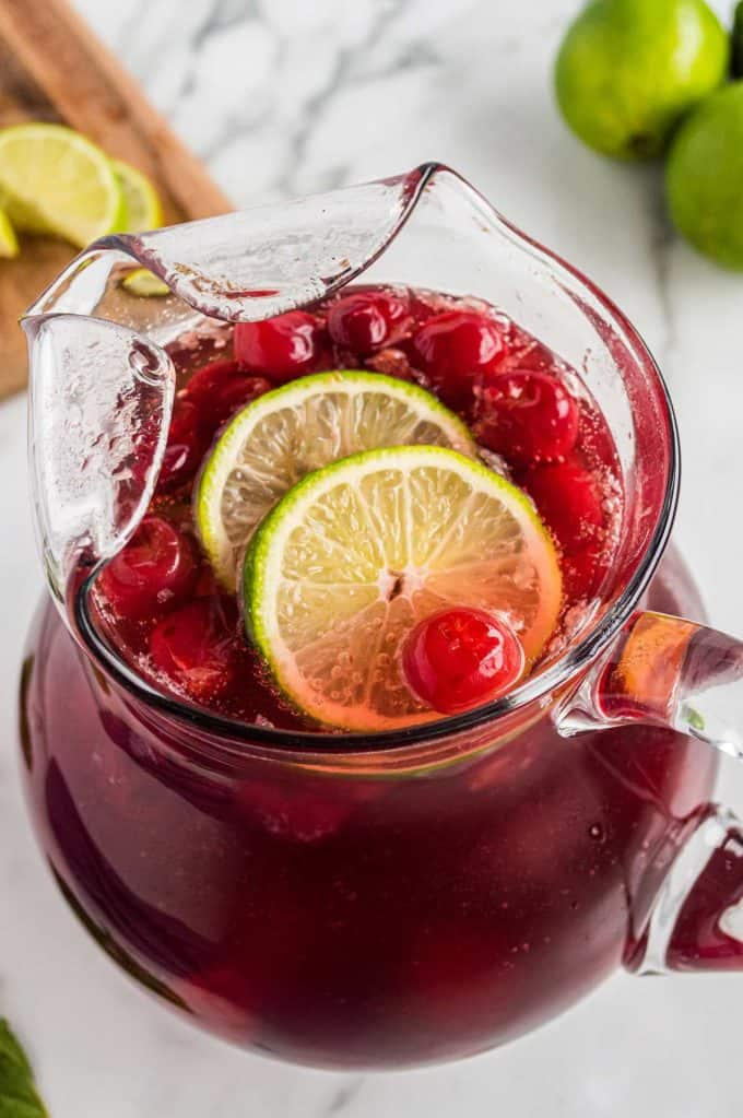 glass pitcher of cherry limeade with lime slices