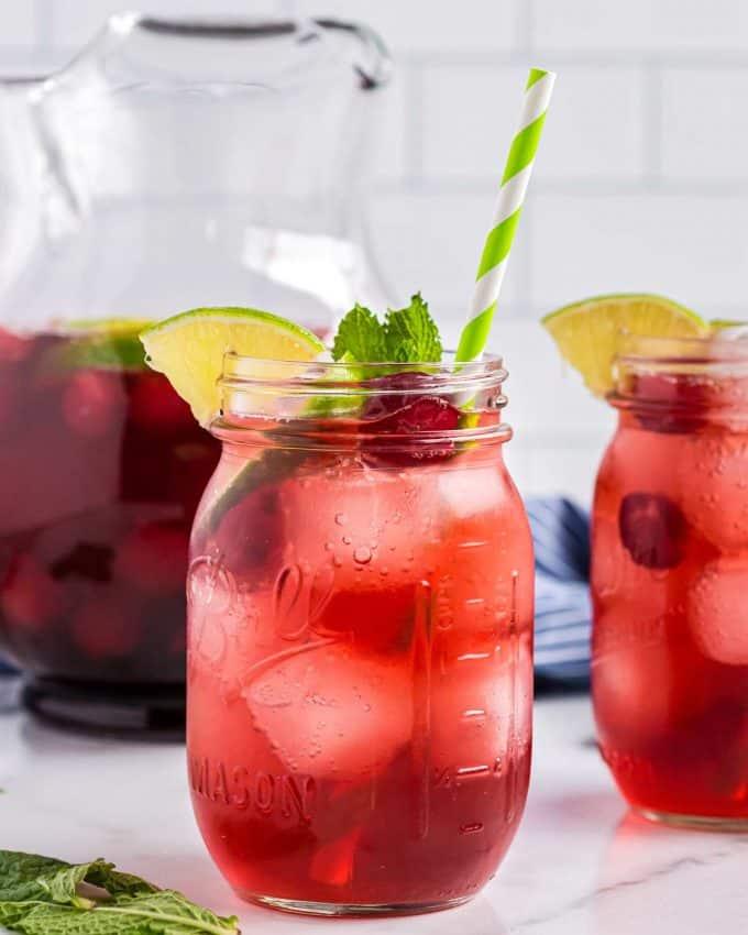 two mason jar glasses of cherry limeade.