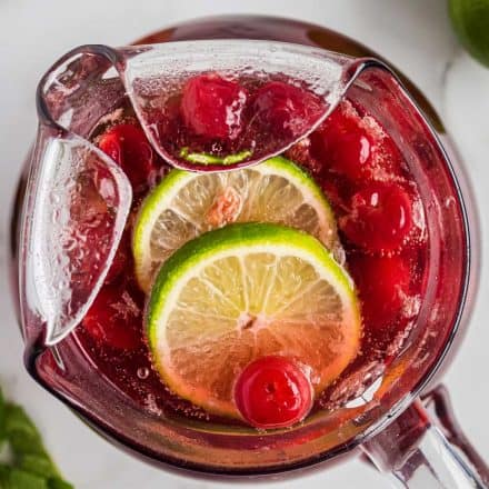overhead view of cherry limeade in a glass pitcher