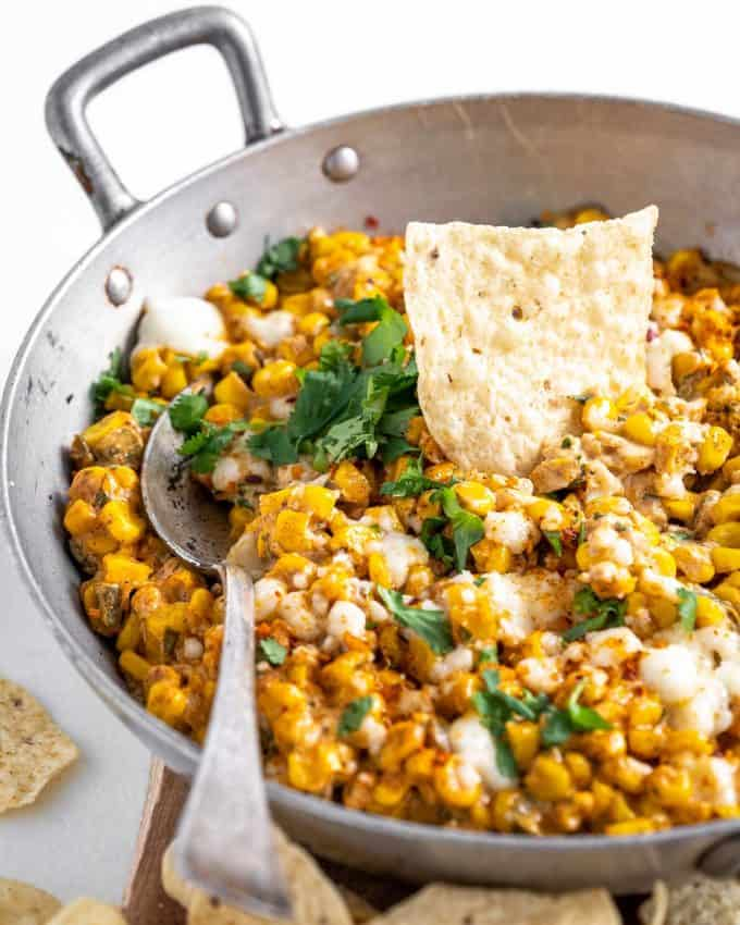 street corn dip in skillet with spoon and chip