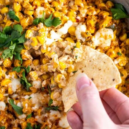 dipping chip into hot street corn dip