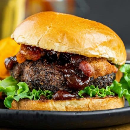 side view of homemade burger with bun on black plate
