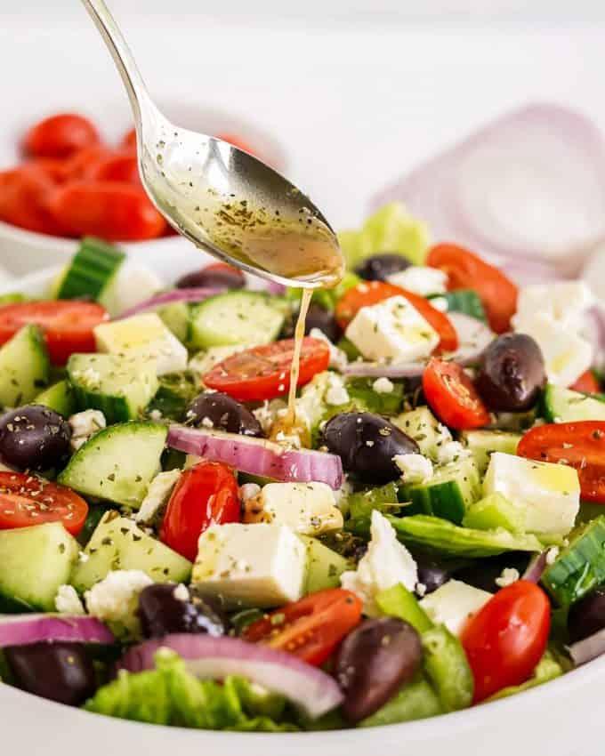 pouring Greek dressing over salad