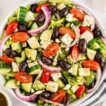 big greek salad in white bowl