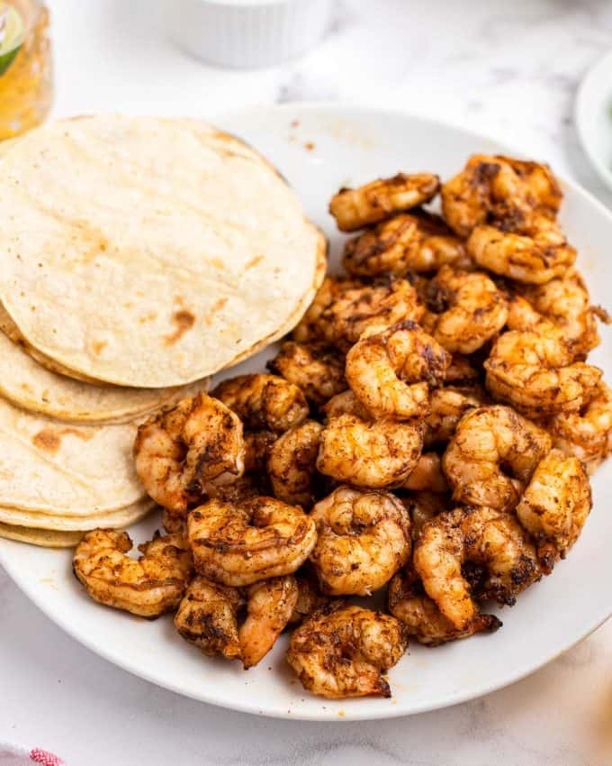 grilled shrimp on plate next to tortillas