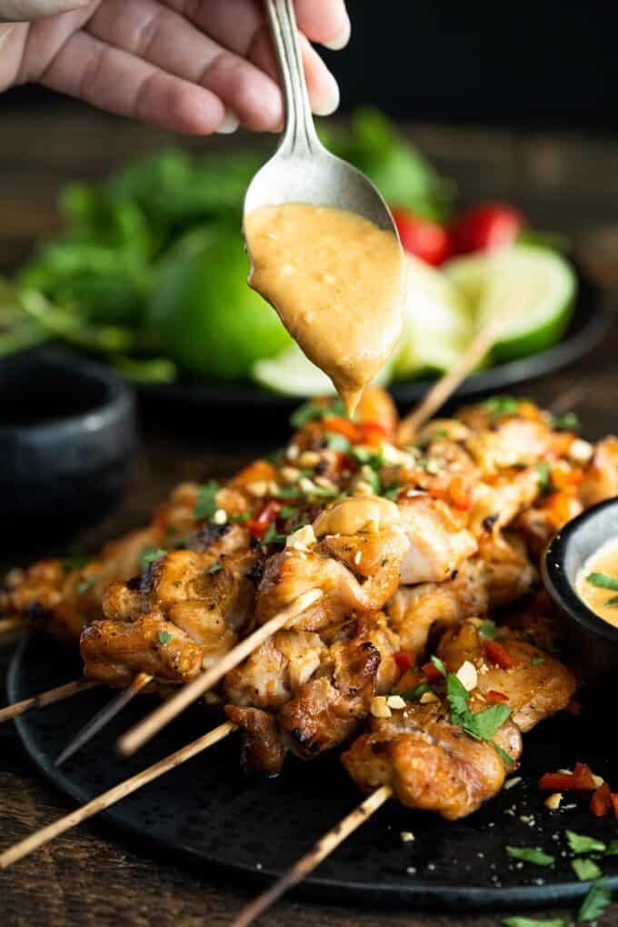 drizzing chicken satay with peanut sauce