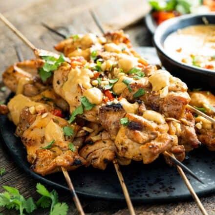 pile of chicken satay skewers on black plate