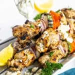 drizzling tzatziki sauce on greek chicken kebabs