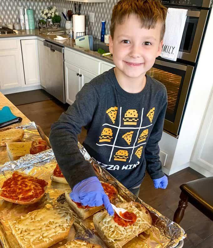 little boy making french bread pizzas