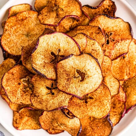 pile of apple chips on white plate