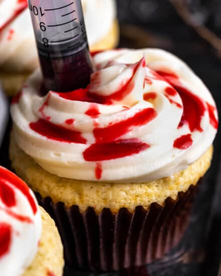 These bloody cupcakes are a delicious way to celebrate Halloween. Moist vanilla cupcakes, smooth vanilla buttercream, and the homemade fake blood really sets the spooky mood! #Halloween #cupcakes #baking