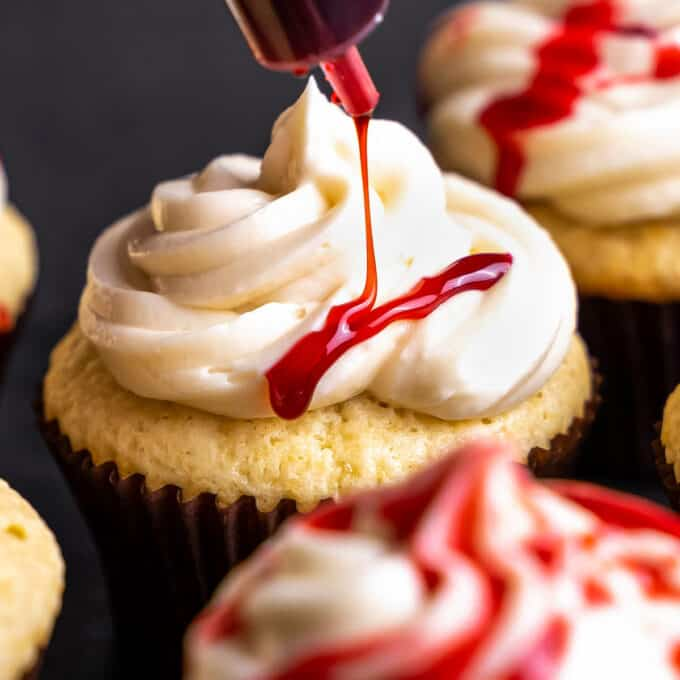 drizzling edible blood over vanilla cupcakes
