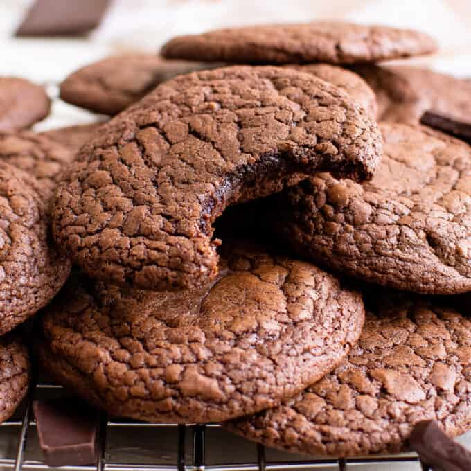pile of brownie cookies and one with a bite taken out of it
