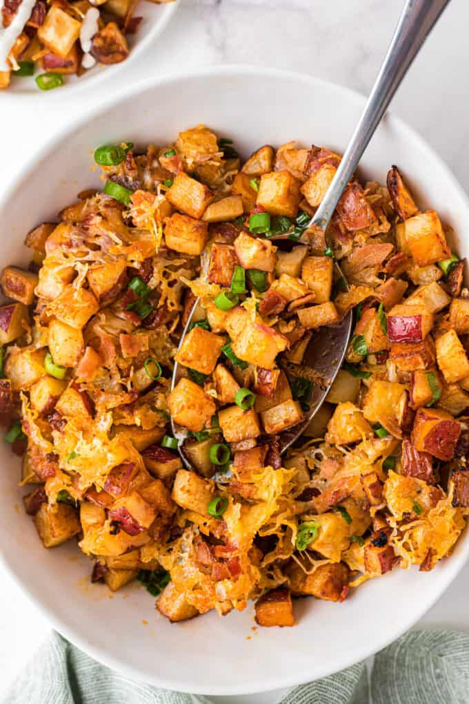 bowl of roasted buffalo potatoes with serving spoon