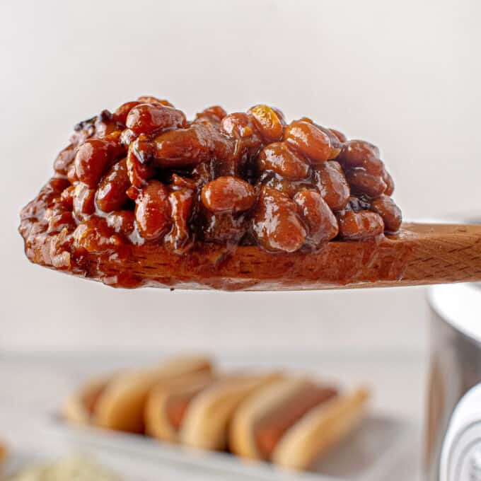scoop of baked beans on wooden spoon