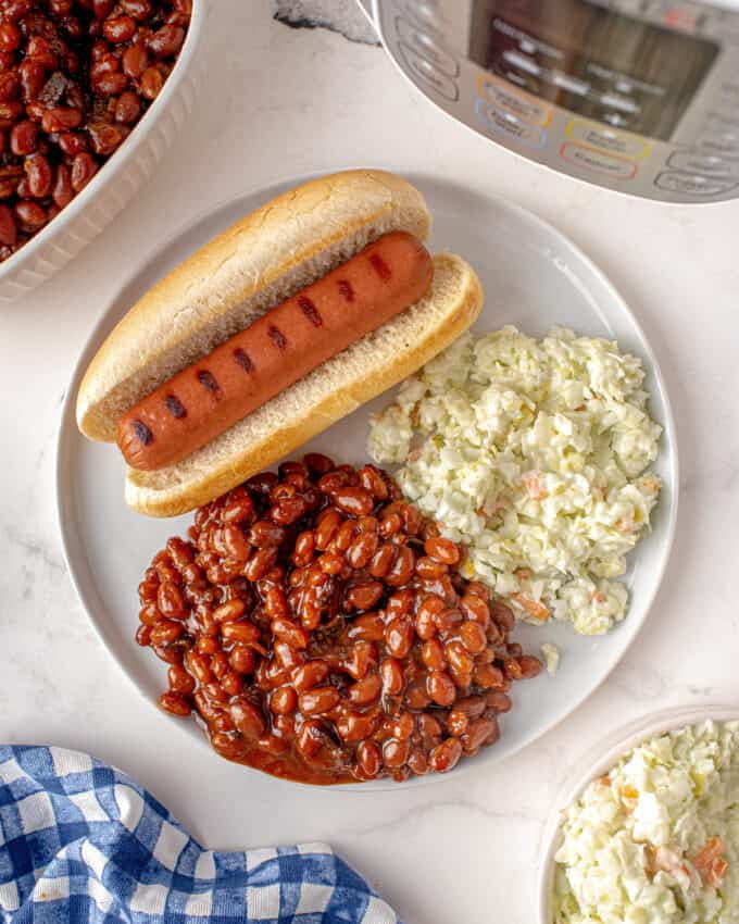 serving of baked beans on plate with hot dog and coleslaw