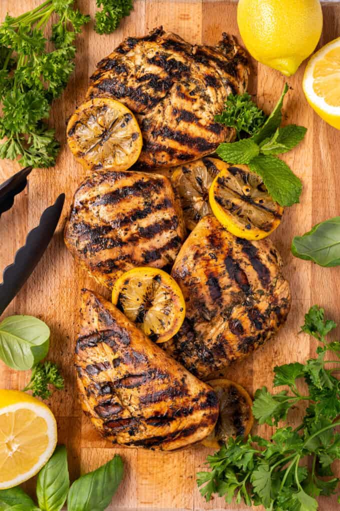 grilled chicken and lemons on a wooden tray