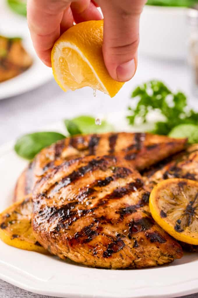 squeezing lemon over grilled chicken