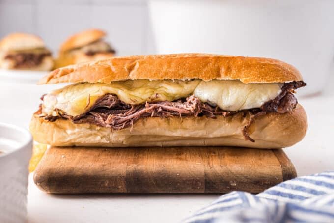 classic french dip sandwich on cutting board
