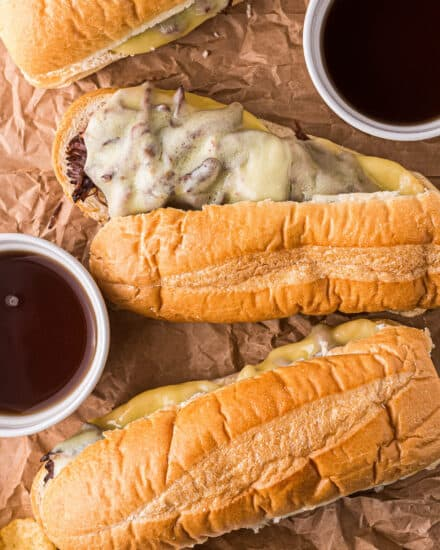 These Slow Cooker French Dip Sandwiches are made with ultra tender roasted beef, melted provolone cheese, soft hoagie bread, and dipped into an amazing au jus sauce. Perfect cold weather comfort food for the whole family! #frenchdip #sandwich #slowcooker #crockpot