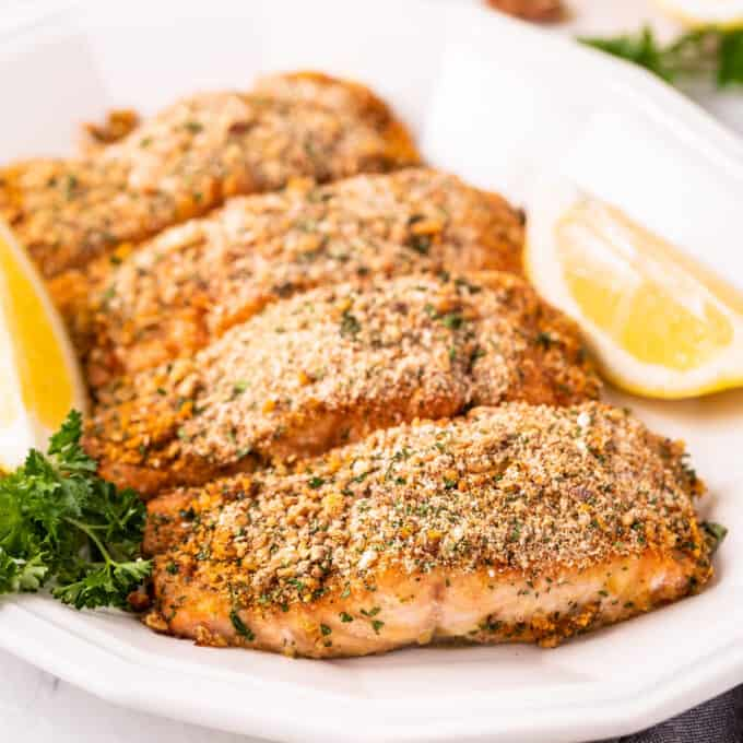 four crusted salmon filets on platter