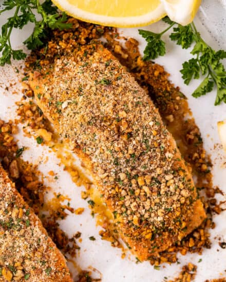 This Baked Crusted Dijon Salmon is light and flaky, and ready in just 30 minutes. Tender salmon filets are brushed with a honey dijon butter, then crusted with a mixture of breadcrumbs, pecans, and herbs and spices. It's the perfect quick and easy weeknight dinner! #salmon #dijon #easydinner