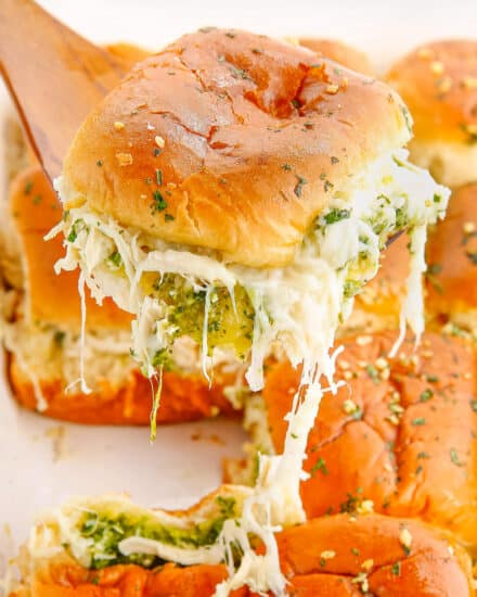 These Cheesy Garlic Pesto Chicken Sliders are gooey, hot, and so easy to make. Made with just 7 simple ingredients, with make ahead and freezer directions, they're the ultimate delicious party food! #sliders #pesto #chicken
