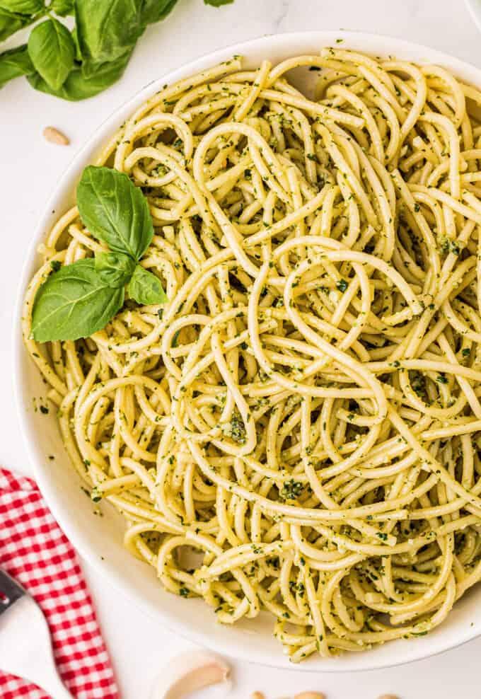 pesto spaghetti in white bowl garnished with basil