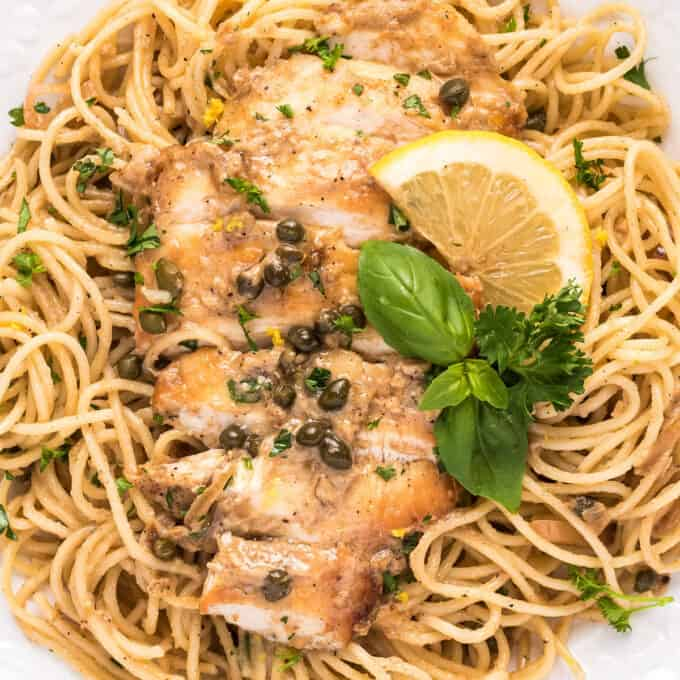 sliced chicken piccata on bed of spaghetti