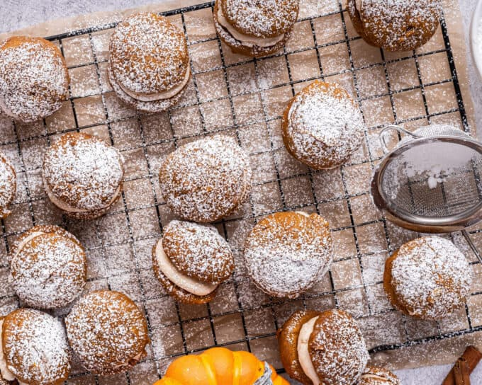 pumpkin whoopie pies on cooling rack dusted with powdered sugar