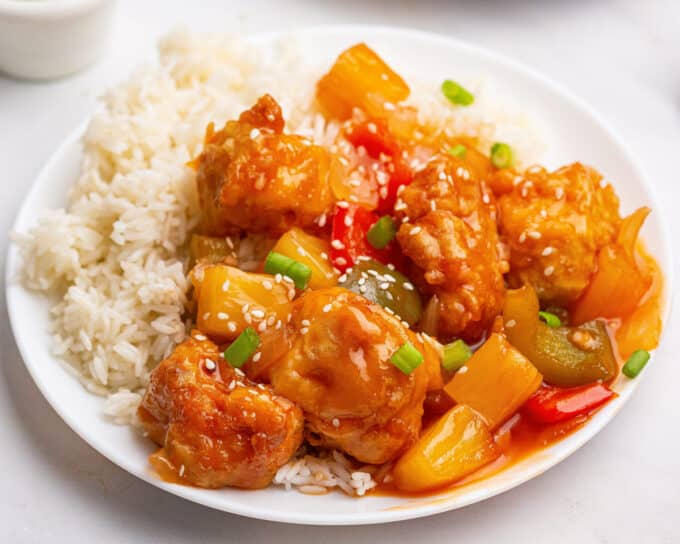 white plate full of white rice and sweet and sour chicken